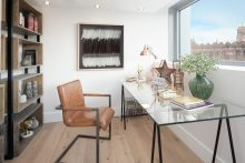 Property PR photograph of study space at CALA Homes The Crescent - a sweeping curve of glass fronted contemporary apartments. Image shows desk and seat, with artwork and bookcases