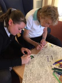 Care PR photography shows Cairn Housing Association's reading project which brings elderly residents together with local primary school children