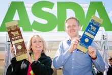 Food and Drink PR photo of Stuart Common (Mackie's Sales Director) and Yvonne McArthur Asda Buying Assistant with giant bars of chocolate, celebrating Mackie's new listing for their chocolate bars