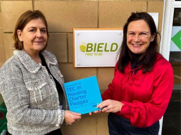 Care PR photo of Lynne Douglas and Geraldine Begg outside of Bield sign with TEC in Housing Charter Pledges Book