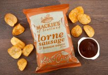 A packet of Mackie's new limited edition Lorne sausage and Brown sauce crisps on a wood backdrop with crisps scattered and a pot of brown sauce
