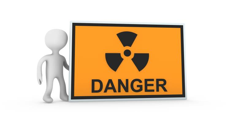 person graphic holding a radiation danger sign