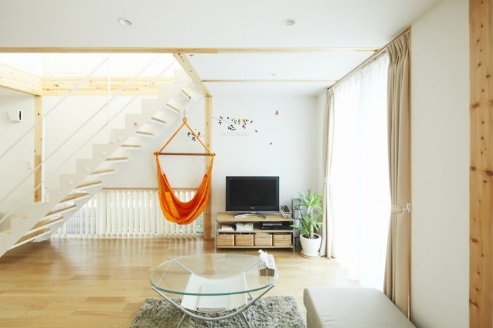 Bare essential furnishings keep this living space from feeling cramped or cluttered letting the beauty of its wood and white elements reflect and bounce the natural light.