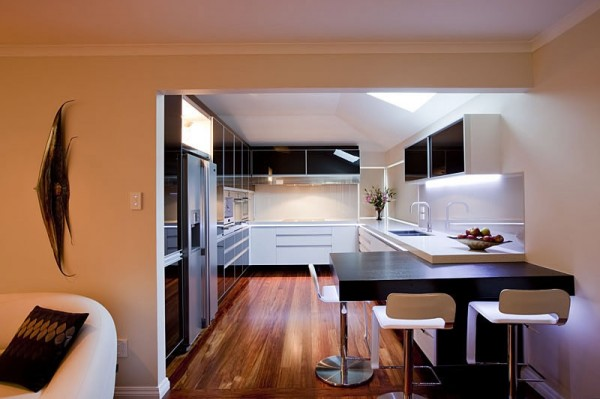 A large skylight and plentiful ambient lighting fill this small windowless kitchen with warm light and a welcoming atmosphere.
