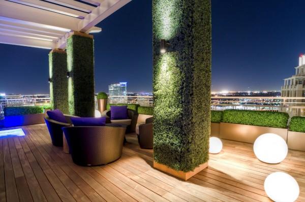 Vivendo colunas cobertas de densa vegetação dar esse espaço ao ar livre moderno um toque natural.  Globos de luz aleatoriamente colocados proporcionar um ar de mistério.