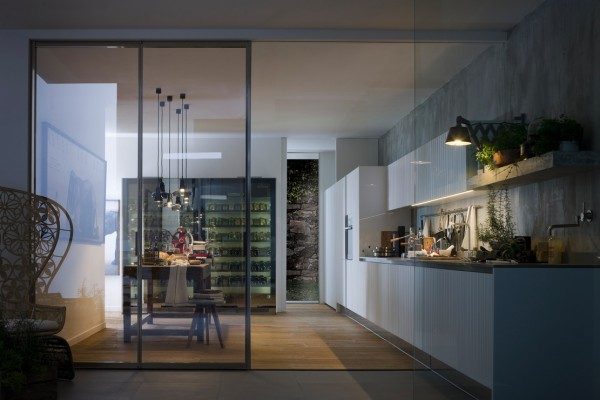 These kitchens have a linear range wall basically keeping the entire kitchen on one side of the room. It makes space for a good sized dining area. The glass walls provide separation without taking away the feel of a large, open space.
