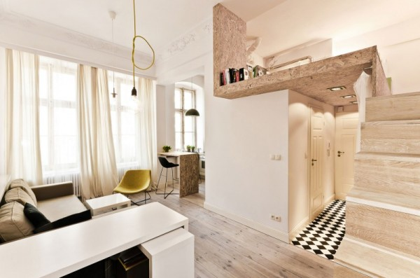 The key to any small apartment is making sure that you make use of vertical space. By tucking a bedroom up a set of narrow stairs, the designers create a makeshift second floor that frees up a lot more living space.