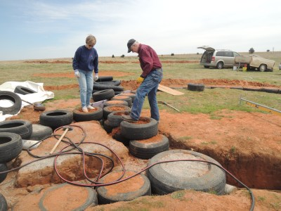 Slamming dirt into tires for foundation of earthbag home