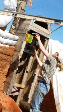 woman throws bucket of dirt to man on earthbag wall