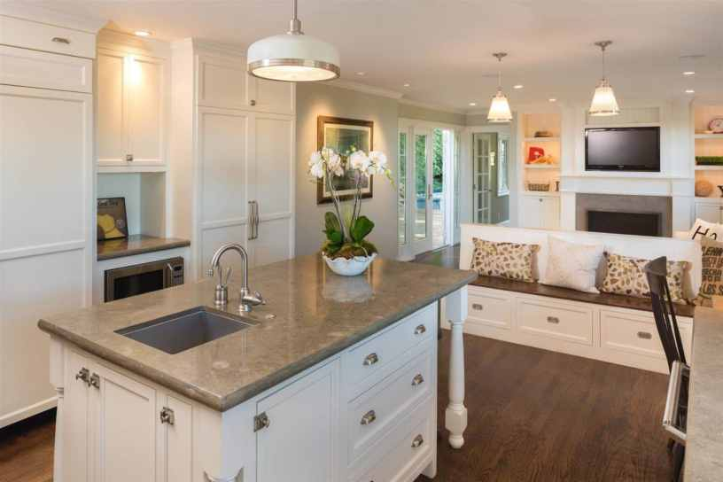 luxurious white open plan kitchen in modern home with granite counter tops and wooden floor