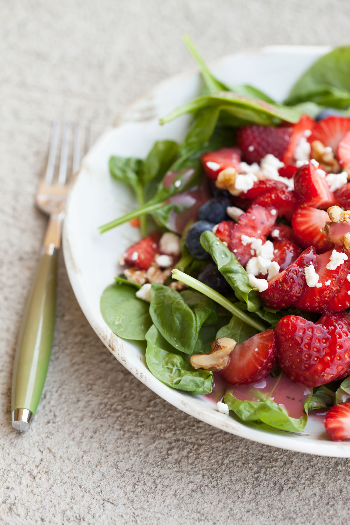Strawberry Blueberry Spinach Salad with walnuts and feta topped with Raspberry Vinaigrette