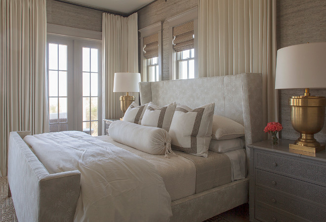 Small Bedroom. This chic small bedroom features a light gray wingback bed dressed in white and gray bedding as well as gray Greek key border pillows flanked by dark gray bamboo nightstands and Large Chunky Urn Table Lamps in Antique Burnished Brass. Windows are dressed in ivory curtains layered over bamboo roman shades. #Smallbedroom #Chicsmallbedroom #bedroom Urban Grace Interiors