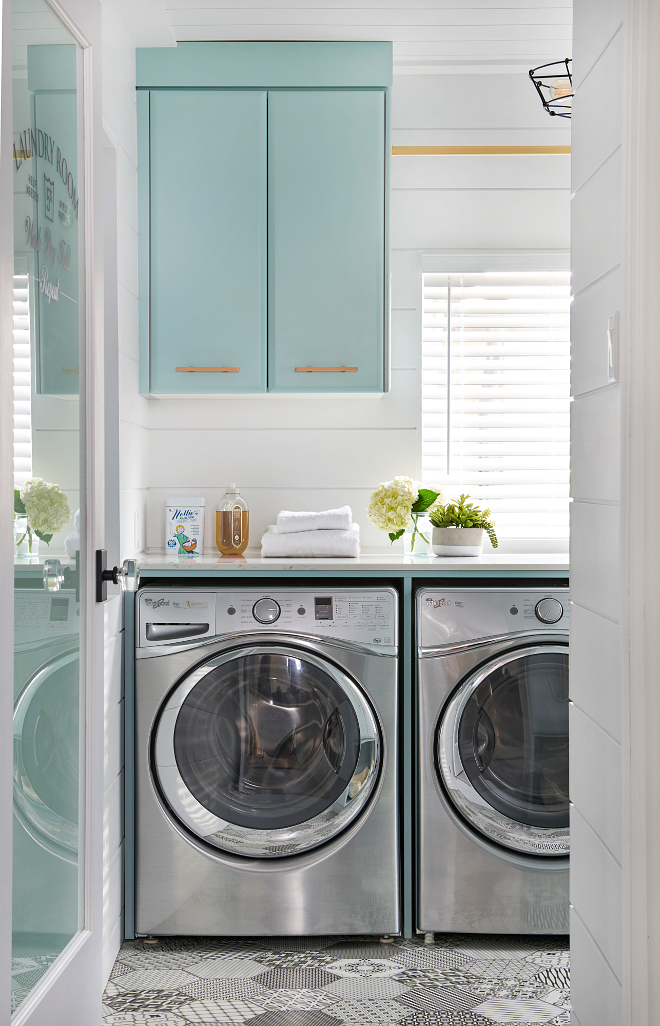 Turquoise Laundry Room Cabinet Paint Color. laundry room boasts a frosted glass etched front door accented with a glass knob opening to black and white mosaic hex floor tiles leading to a silver front loading washer and dryer enclosed beneath a white quartz countertop fixed beneath a window. The window is framed by a horizontal shiplap trim and located beneath a brass drying rod fixed to blue cabinets painted in Benjamin Moore Gossamer Blue and finished with brass pulls. #Laundryroom #turquoisecabinet #Turquoise #brasshardware #hardware Soda Pop Design Inc.