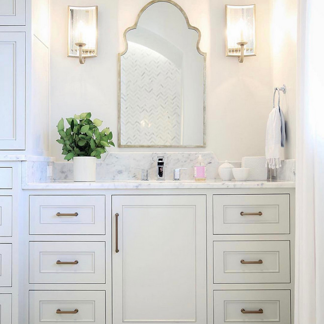 Bathroom Mirror and Sconces. In this bathroom, a Moroccan mirror add gorgeous curvilinear shape and shine in combination with the antiqued mirrored sconces. Mirrors: Wisteria. Sconces: Currey and Co. #Bathroom #Mirror #Sconces Old Seagrove Homes