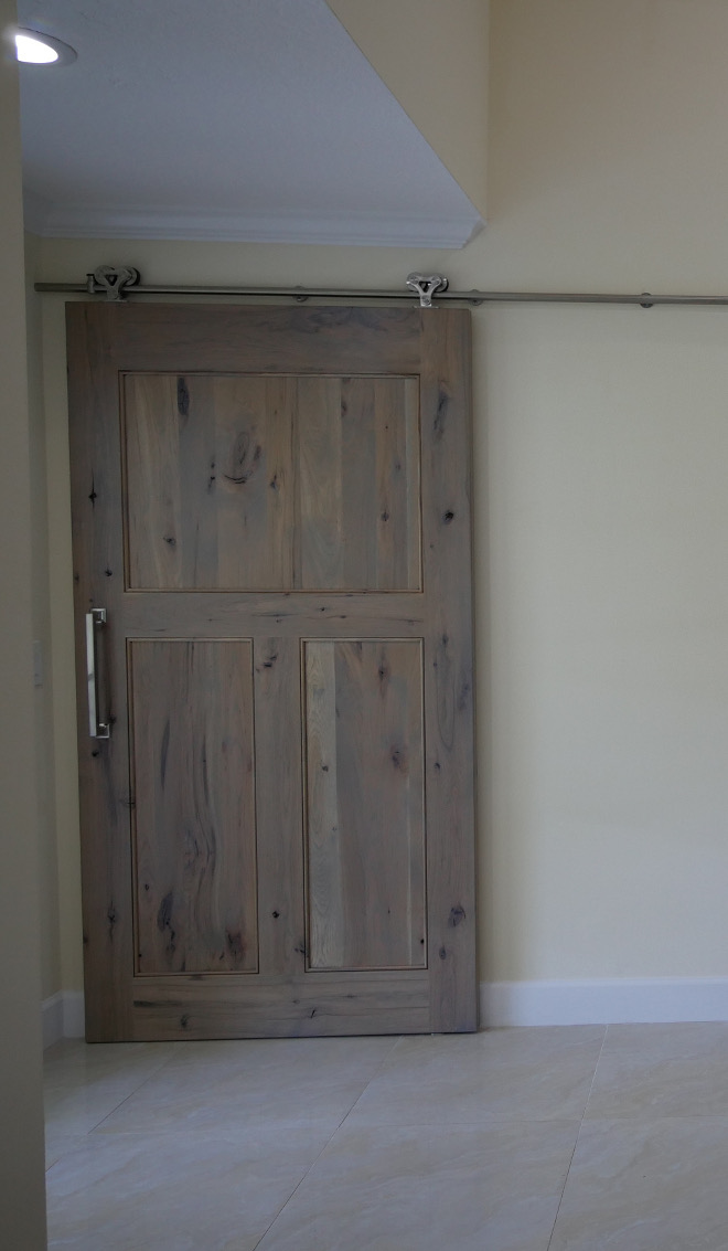 Driftwood Barn door. This summer the couple decided to carry the rustic hickory further into the house with the addition of a barn door concealing the laundry room. This 140LB. solid hickory door is a wonderful sight upon entering this gorgeous home. Barn Door: Crystal Cabinets, Rustic Hickory, Driftwood Stain with Brown Brushing. Barn Door Hardware: Hickory Hardware, Studio Collection #DriftwoodBarndoor Waterview Kitchens