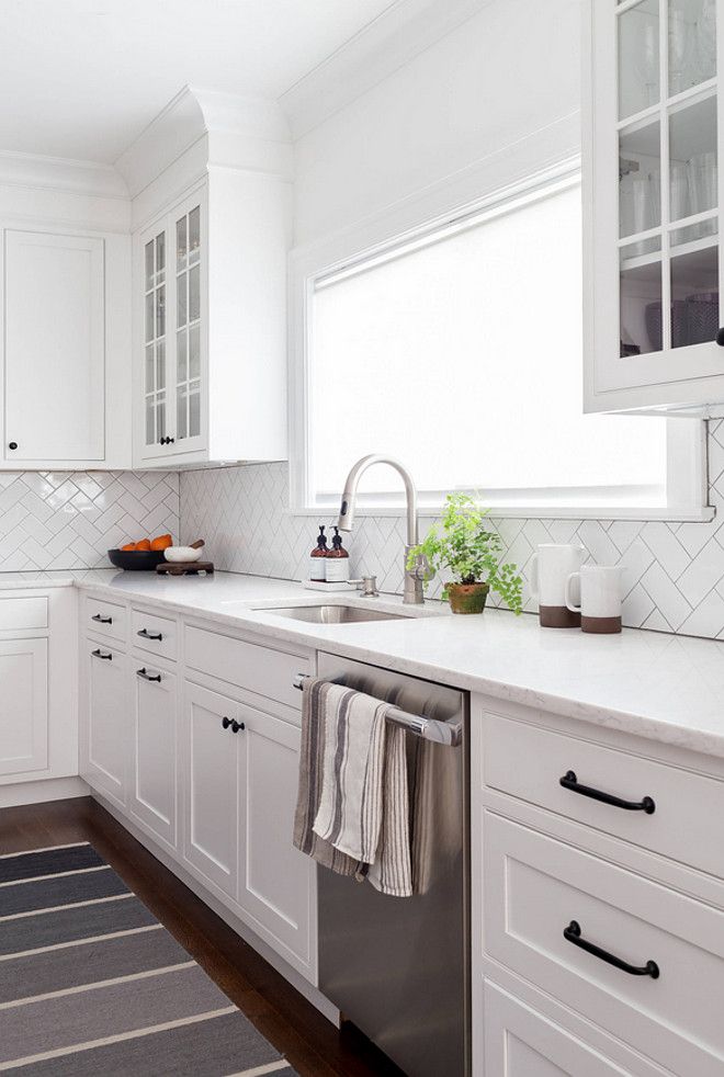 Shaker Kitchen Cabinets with simple herringbone subway tile and white marble countertop. Shaker style cabinets are painted in Benjamin Moore Decorator's White #BenjaminMooreDecoratorsWhite #shakercabinet #shakerkitchen #shakerkitchencabinets #simplebacksplash #backsplash #subwaytile #herringbone #whitemarble Chango & Co.