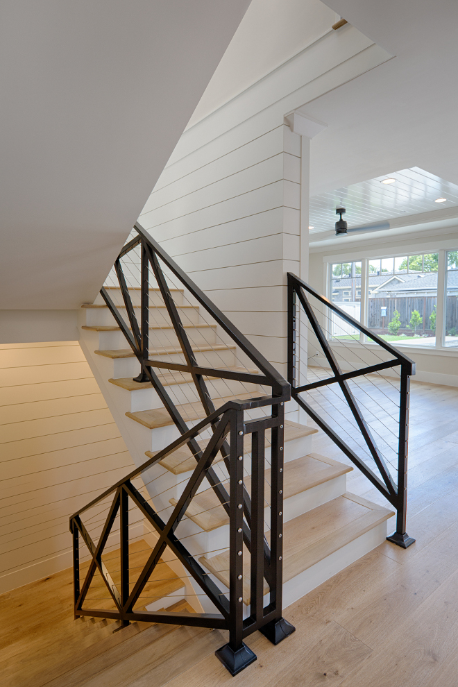 Farmhouse staircase. Metal farmhouse staircase. This farmhouse stair is made of black steel, crossed barn look guardrails and steel cable wire. Walls are shiplap. Farmhouse stair made of black steel, crossed barn look guardrails with steel cable wire and shiplap walls. #farmhousestair #staircase #farmhousestaircase #crossedstaircase #steelcablestaircase AK Construction