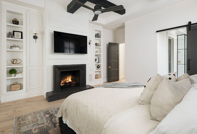 Modern Farmhouse Bedroom Fireplace. One of our favorite features in this master bedroom is the Basalt stone fireplace surround selected by the interior designer. The black wood beams in the ceiling continue our black/white theme throughout this custom home. Another fun feature is the decorative bookcase on either side of the fireplace. Modern Farmhouse Bedroom Fireplace. Modern Farmhouse Bedroom Fireplace. Modern Farmhouse Bedroom Fireplace Modern Farmhouse Bedroom Fireplace Modern Farmhouse Bedroom Fireplace #ModernFarmhouse #Bedroom #Fireplace A Finer Touch Construction