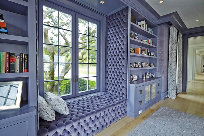 Purple Library Cabinets with tufted window-seat flanked by custom bookcases