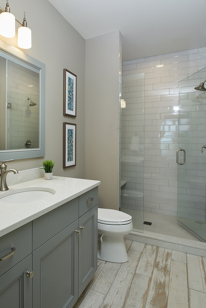 Arctic Gray by Benjamin Moore grey bathroom with distressed wood-looking tile Arctic Gray by Benjamin Moore grey walls and distressed wood-looking tile Cabinet paint color is Benjamin Moore Gray Pinstripe 1588 #BenjaminMoore #Benjaminmoorepaintcolors