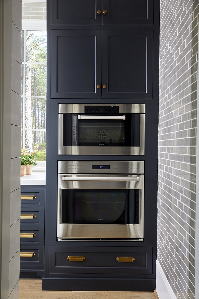 Midnight Oil by Benjamin Moore A pantry with its own farmhouse sink and built-in ovens is located behind the range wall Paint Color is Midnight Oil by Benjamin Moore #BenjaminMoore #pantry
