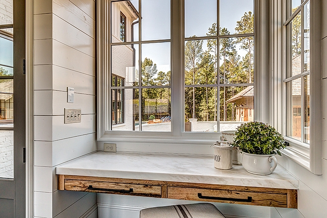 Floating Desk Drop zone with floating desk Mudroom drop zone with reclaimed White Oak floating desk with white marble countertop and shiplap walls windows looking towards backyard #floatingdesk #dropzone #mudroom #desk #whiteoak #reclaimedwood