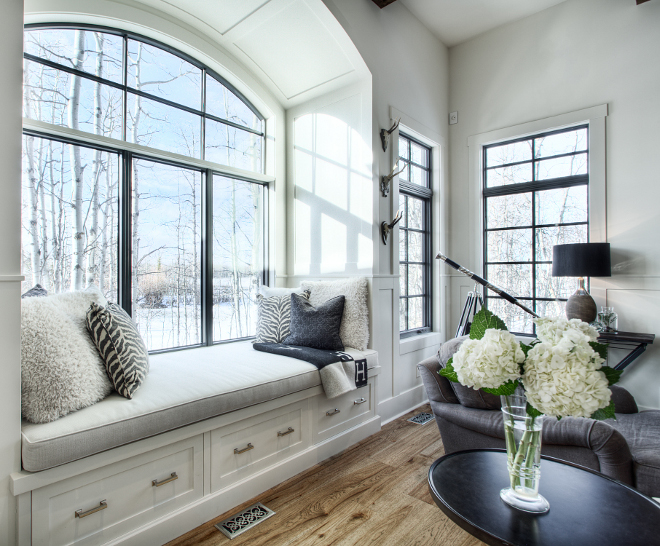 Arched Window-seat Great room with built-in day bed featuring a barrel arch and wainscoting throughout and black windows #windowseat #blackwindows #archedwindow