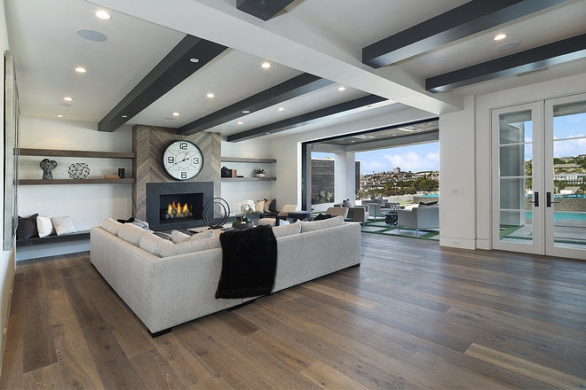 Basement Family Room with reclaimed wood chevron shiplap fireplace, ceiling beams and white oak hardwood flooring