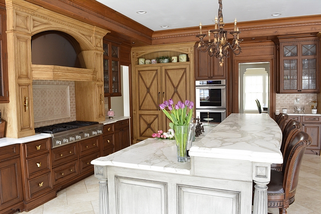The kitchen island is 9 feet long, two tiered, and is made up of double stacked honed Calcatta marble The cabinetry is a distressed weathered grey