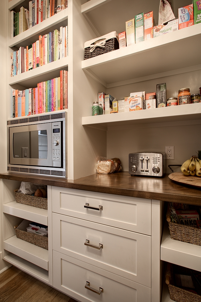 Pantry features pull out baskets, ample storage, and built-in microwave with cookbook storage above #pantry #cookingbooks