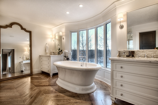 French Bathroom French Bathroom Design French Master Bathroom with paneled walls inset mirrors free standing tub and chevron hardwood flooring #Frenchbathroom #bathroom #chevronflooring