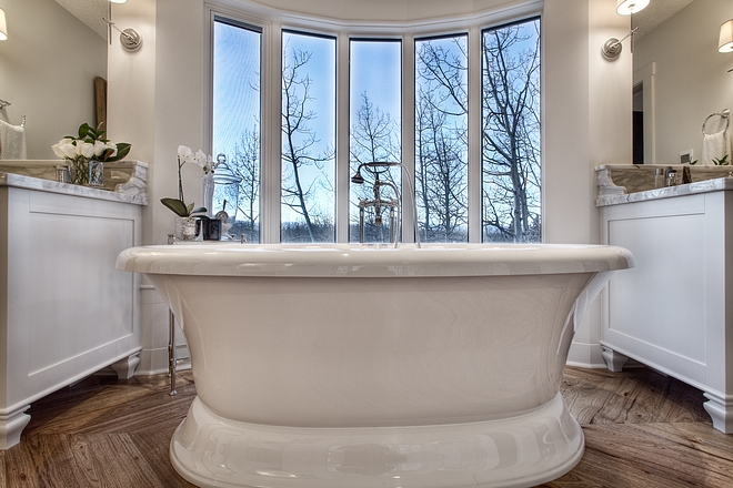 French bathroom with freestanding bath by floor to ceiling windows all sources on Home Bunch #Frenchbathroom #freestandingbath #bathroomwindows