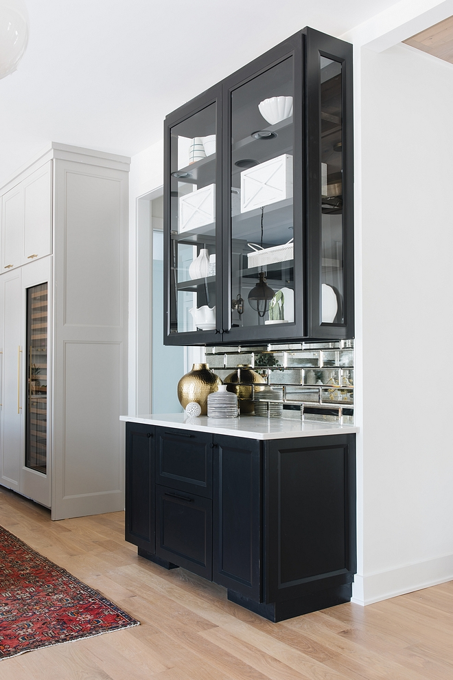 Kitchen Hutch The kitchen hutch features three-sided glass cabinets, quartz countertop and antique mirrored subway backsplash The white decor brings some contrast to the black cabinets #kitchen #hutch