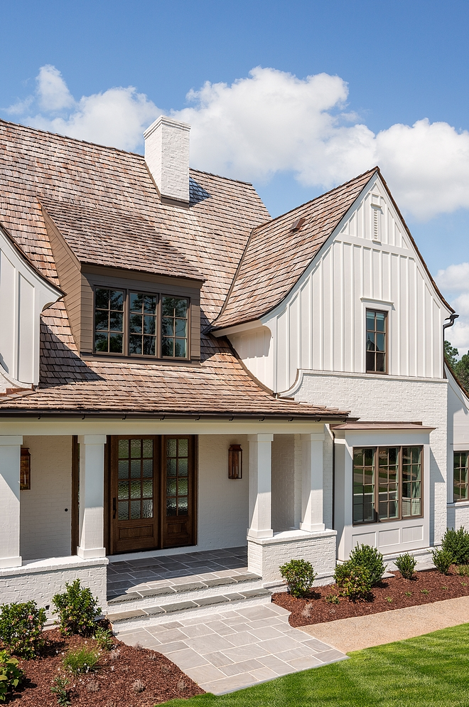 Modern Farmhouse exterior with classic elements such as Painted Brick Board and Batten Siding Cedar Shake Roofing and painted windows sources on Home Bunch #modernfarmhouse #farmhouse #exteriors #paintedbrick #boardandbatten
