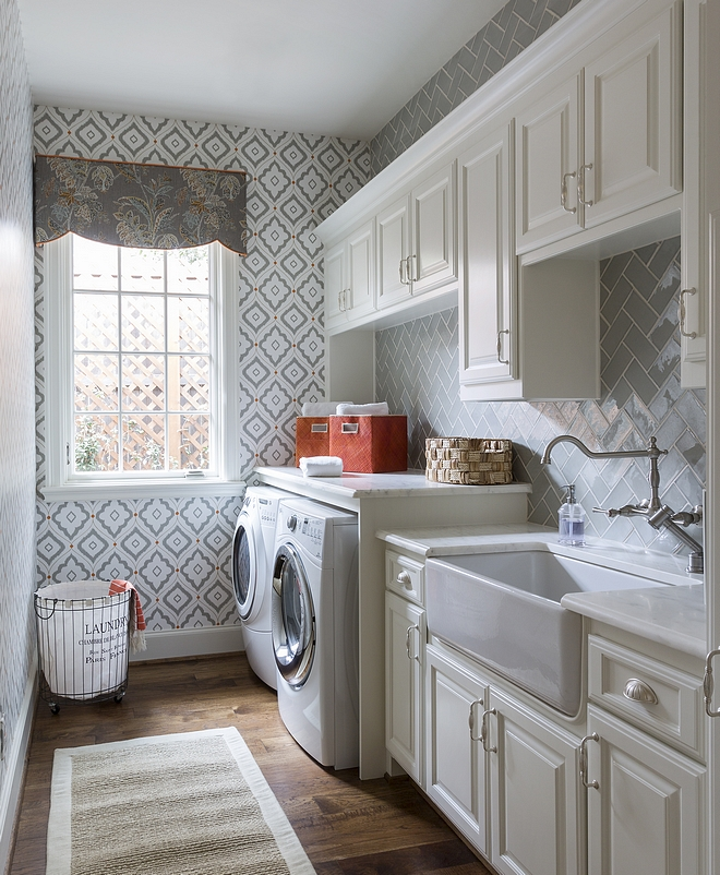 Laundry Room Sherwin Williams Alabaster Laundry room features off-white cabinets, painted in Sherwin Williams Alabaster SW 7008, hardwood floors, white marble countertop, farmhouse sink and a grey backsplash tile in herringbone pattern #laundryroom #SherwinWilliamsAlabaster