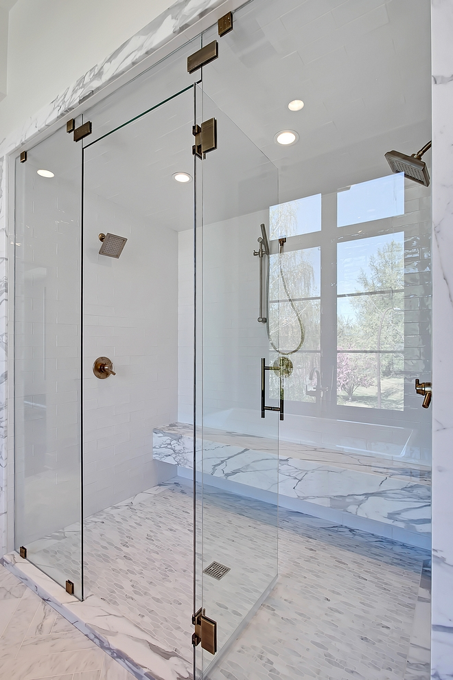 Shower Tile Master Bathroom shower tile The master bathroom shower features 3x12 Cotswold white tile for walls and ceiling (steam unit), solid Statuario marble bench, Carrara long octagon mosaic for the shower base #masterbathroom #showertile