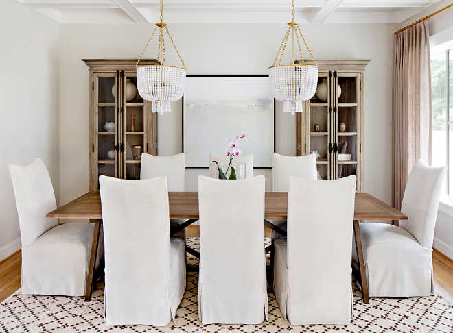 Dining Room Two Chandeliers This is the type of dining room I love - it's very comfy and it feels collected without being too precious #diningroom #chandeliers #linenchairs #cofferedceiling #rug #diningtable #linencurtains