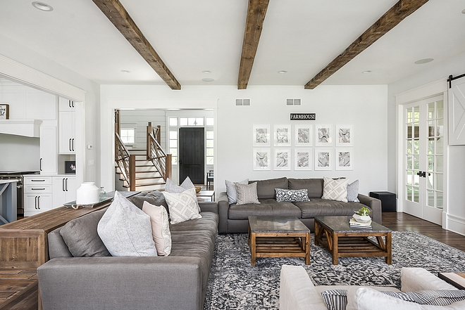 Farmhouse living room with beams and white walls painted in White Dove by Benjamin Moore Decor sources on Home Bunch