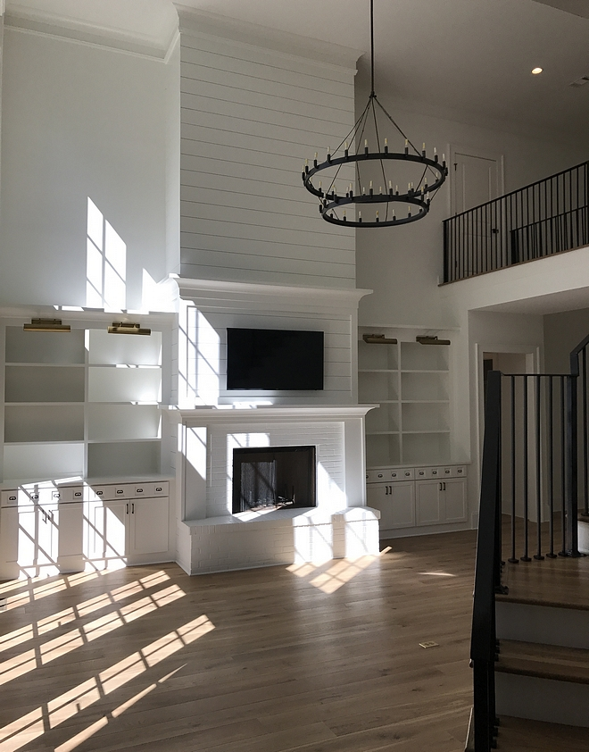 Living Room tall shiplap Built-ins add to the livability to the space while a tall fireplace balances the high ceiling Fireplace Tall fireplace with shiplap paneling Living room high ceiling fireplace #tallfireplace #highceiling #livingroom #fireplace