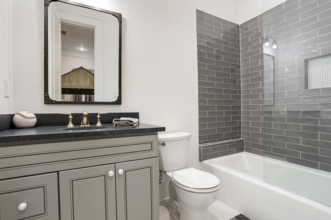 Boys bathroom with black countertop, grey vanity and charcoal grey subway tile
