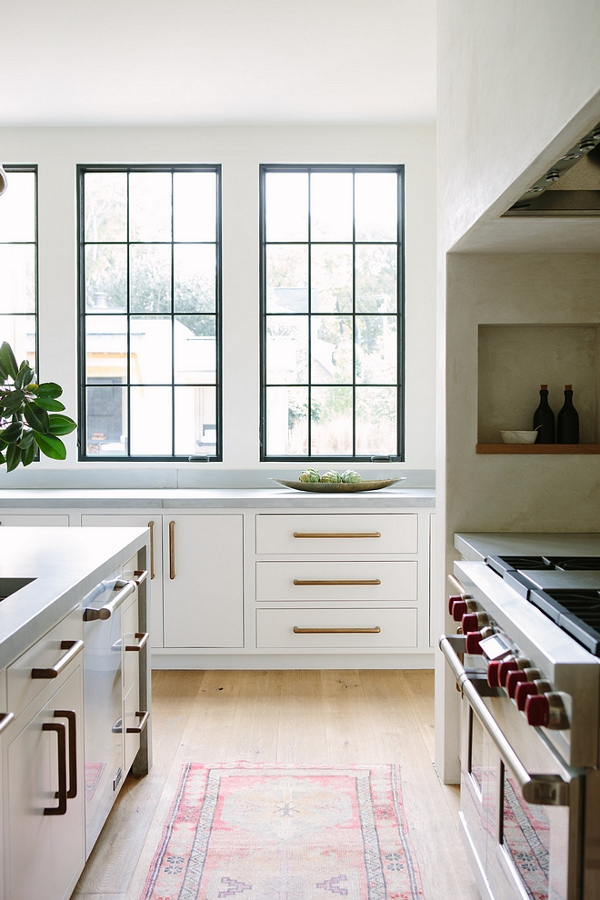 White Kitchen Minimalist White Kitchen with white cabinetry painted in White Dove by Benjamin Moore, black windows and concrete countertop #minimalistkitchen #WhiteDovebyBenjaminMoore #blackwindows #concretecountertop