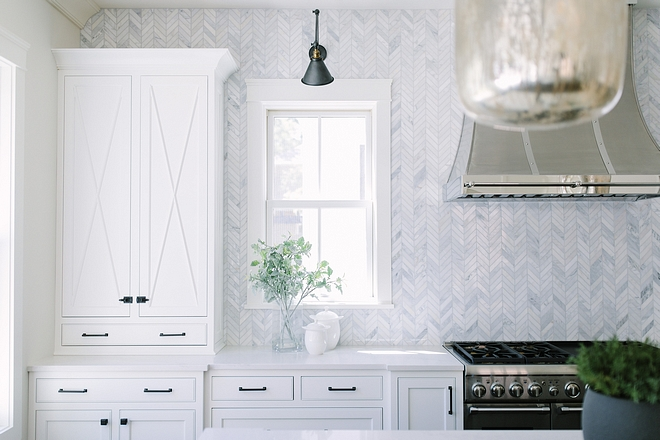 Backsplash is Carrara marble tiled backsplash to ceiling in Chevron Pattern #Backsplash #Carraramarbletiled #kitchenbacksplash #ChevronPattern