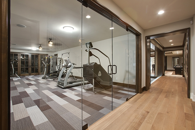 The exercise room features custom stained wood with walls painted in BM Collingwood OC-28