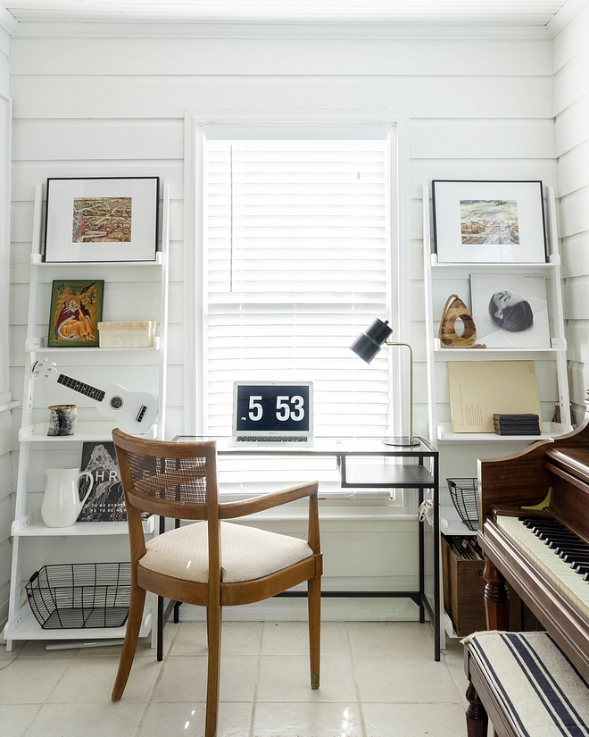 Small sunroom used as a home office with bookcases flanking a window and a metal and glass desk with vintage cane back chair