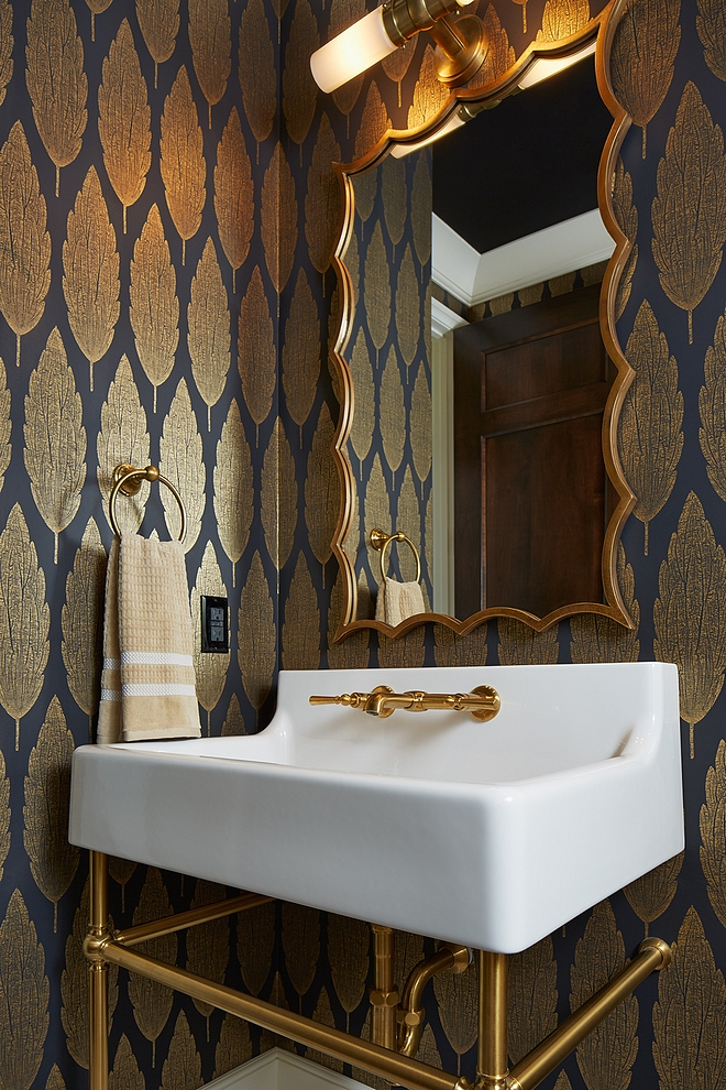 Located just off the mudroom, this powder room is elegant and features a gorgeous wallpaper, curved brass mirror and a brass base washstand #bathroom