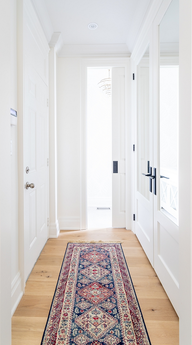 Hallway with closet with mirrored doors and vintage hall runner All of the wainscoting and millwork is painted Benjamin Moore Simply White same as the wall colour #hall #hallway #millwork #BenjaminMooreSimplyWhite