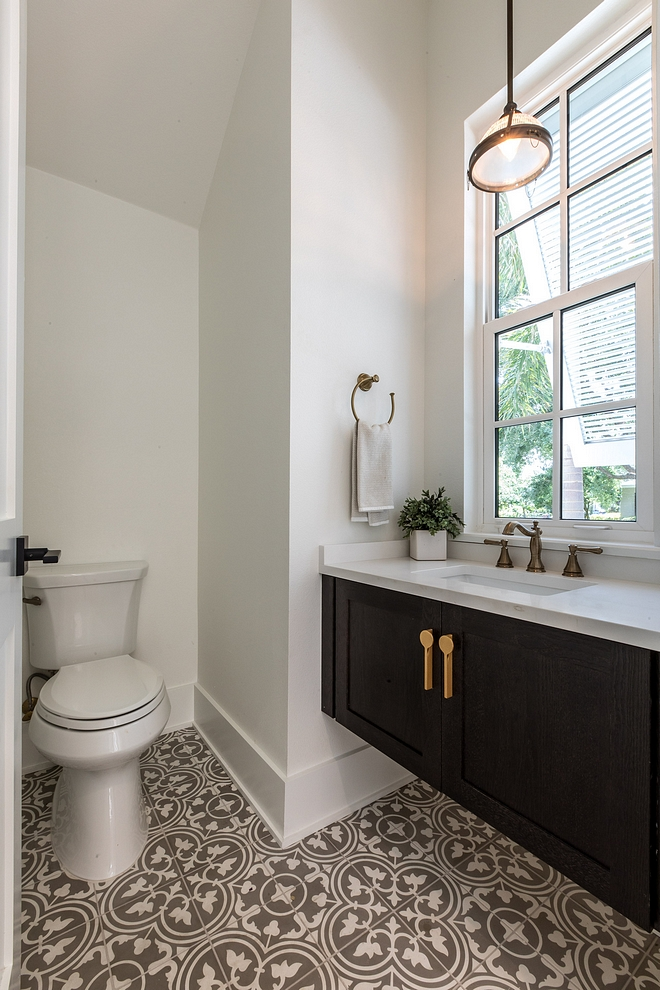 The powder room features a floating vanity with quartz countertop and grey and white cement tile #powderroom #floatingvanity #cementtile