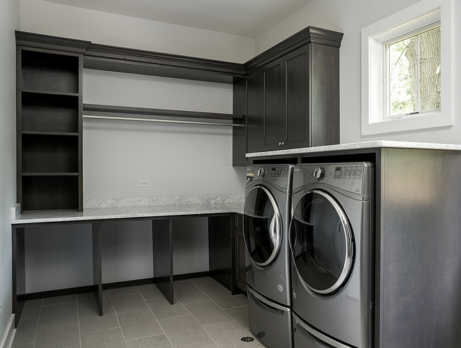 The laundry room features open space for hampers under the counter