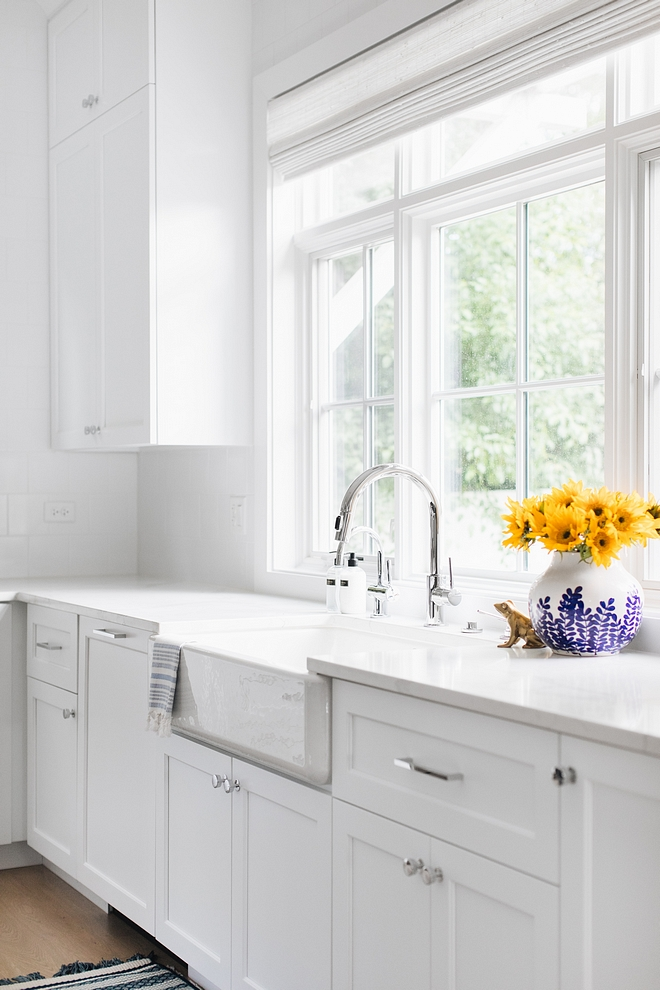 White kitchen painted in Extra White by Sherwin Williams with marble quartz countertop, fireclay farmhouse sink and an arched kicthen faucet #kicthen #kitchen #ExtraWhitebySherwinWilliams