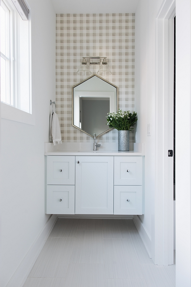 The kids' bathroom feature custom floating vanity and a gingham wallpaper. Countertop is Snow White quartz and the vanity paint color is SW Extra White